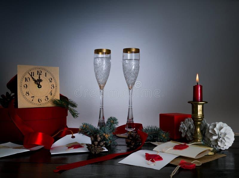 Antike Gläser der Weinlese auf Weihnachtstabelle mit Kerze, Uhr, Buchstaben, Umschlägen und Einladungen Santa Claus stockfotografie