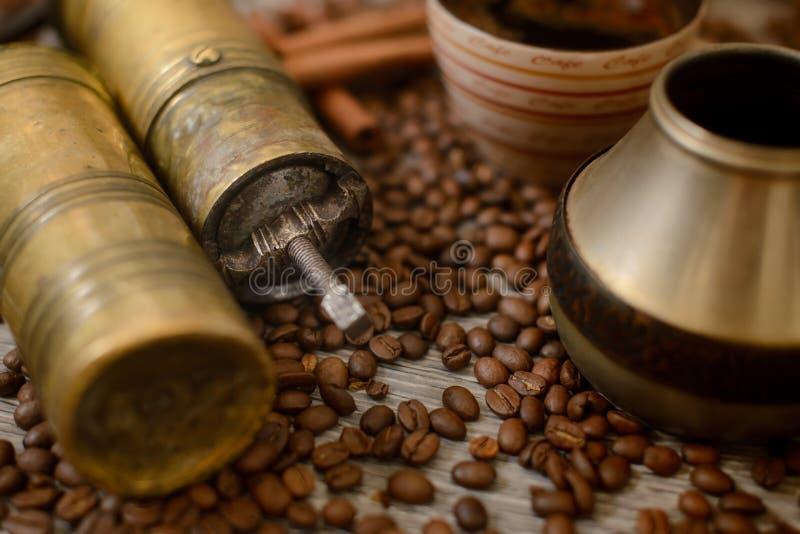 Antike Kaffeemühle mit Schale, Kaffeemaschine und Bohnen lizenzfreie stockfotografie