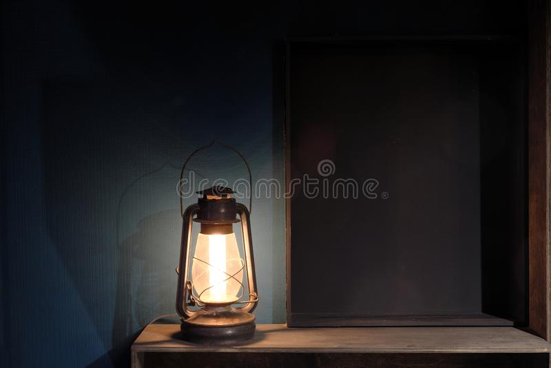 Antike Kerosinlampe der Weinlese gegen eine dunkelblaue Wand Hölzerne Regale stockfoto