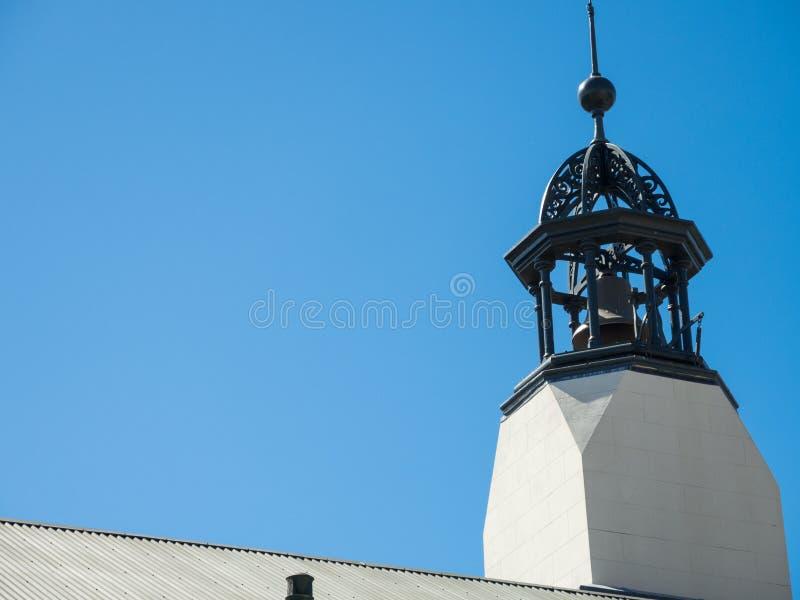 Antike Metallglocke auf die Oberseite eines Altbaudachs mit blauem Himmel im Hintergrund lizenzfreie stockfotos