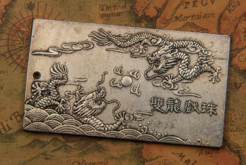 Antike silberne Platte mit kämpfenden Drachen auf alter orientalisch-ähnlicher Weltkarte lizenzfreies stockbild