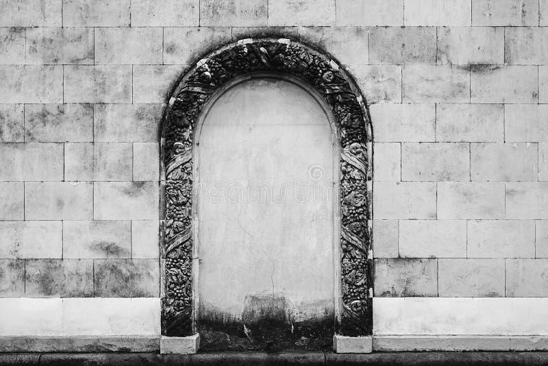 Antike Steinwand mit Verzierungsbogen in der Mitte stockfotografie