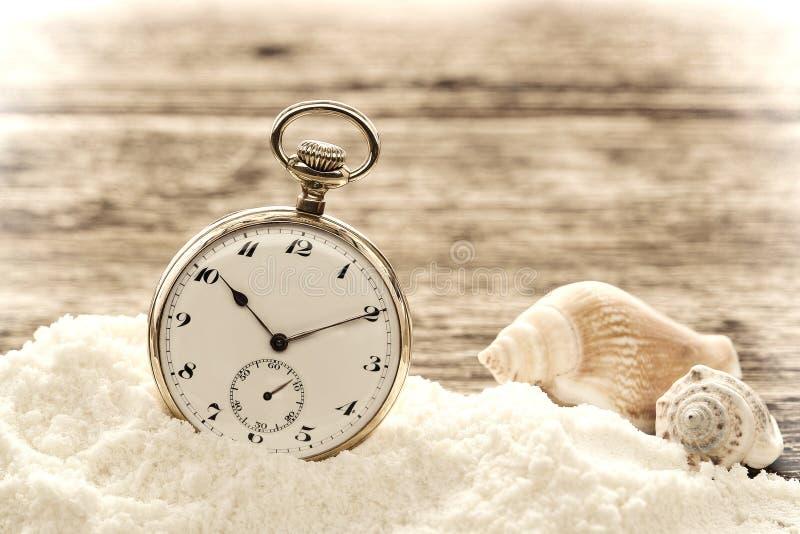 Antike Taschen-Uhr im Sand auf gealterten hölzernen Vorständen stockfotos