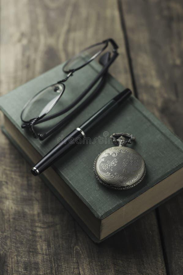 Antike Taschenuhr, -gläser und -buch lizenzfreie stockfotografie