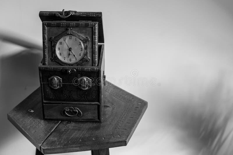 Antike Uhr, die auf einer alten Tabelle sitzt lizenzfreie stockfotografie