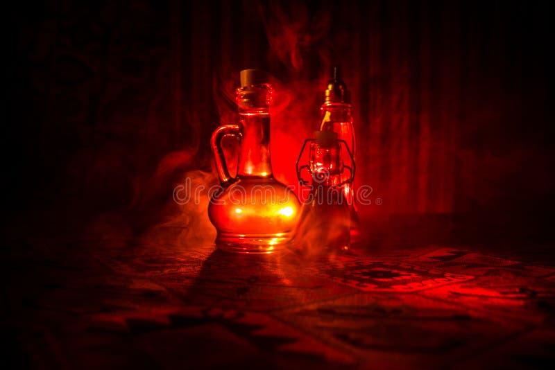 Antiken- und Weinleseglasflasche auf dunklem nebeligem Hintergrund mit Licht Gift oder Magieflüssigkeitskonzept stockfoto