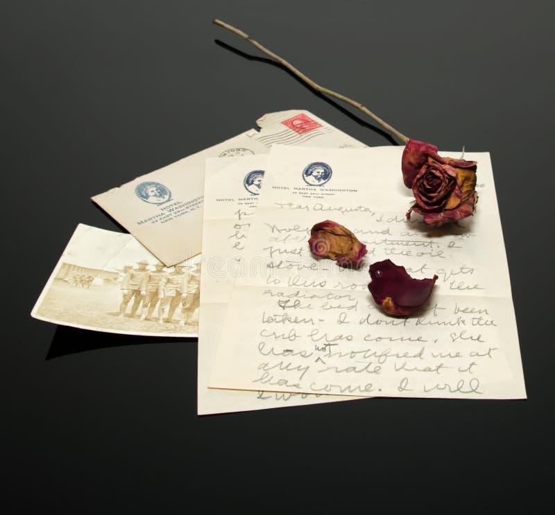 Antiker Buchstabe mit WWI-Bild und einer verblaßten und getrockneten roten Rose stockbilder