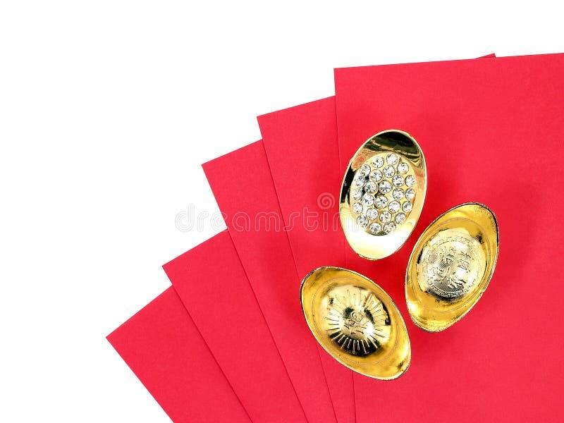 Antiker chinesischer Goldbarren auf dem roten Umschlag, der auf chinesischen Schriftzeichen des weißen Hintergrundes lokalisiert  stockfotografie
