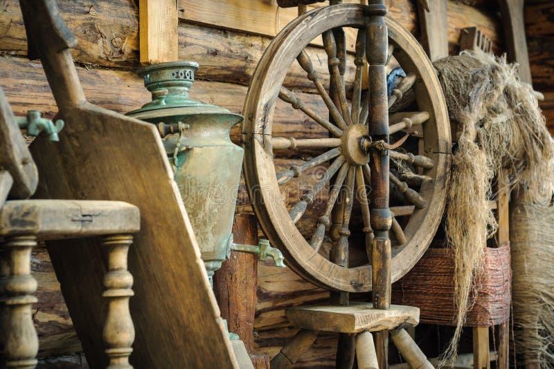 antikes hölzernes Spinnrad mit Zusätzen und alten Haushaltsartikeln gegen eine raue hölzerne Klotzwand stockfotos