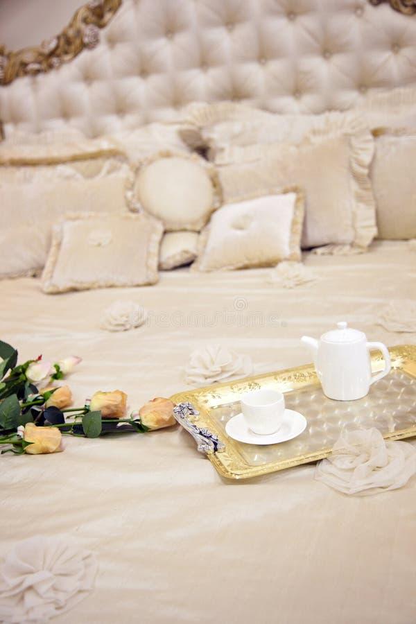 Antikes Luxusbett mit Rosen lizenzfreie stockfotos