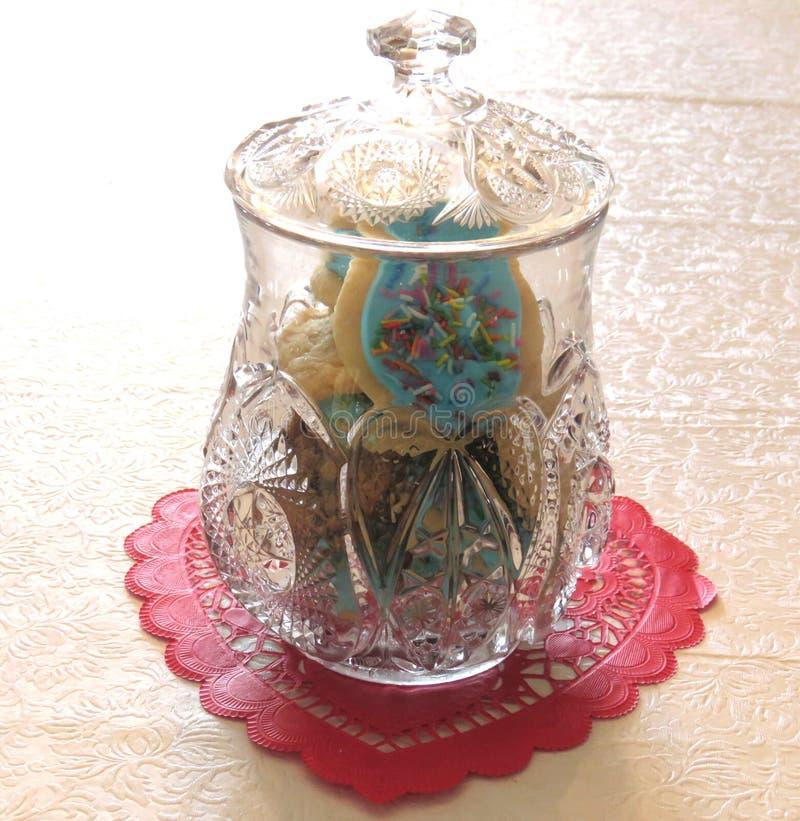Antikes Plätzchenglas, das auf rotem Valentinsgruß sitzt lizenzfreies stockbild