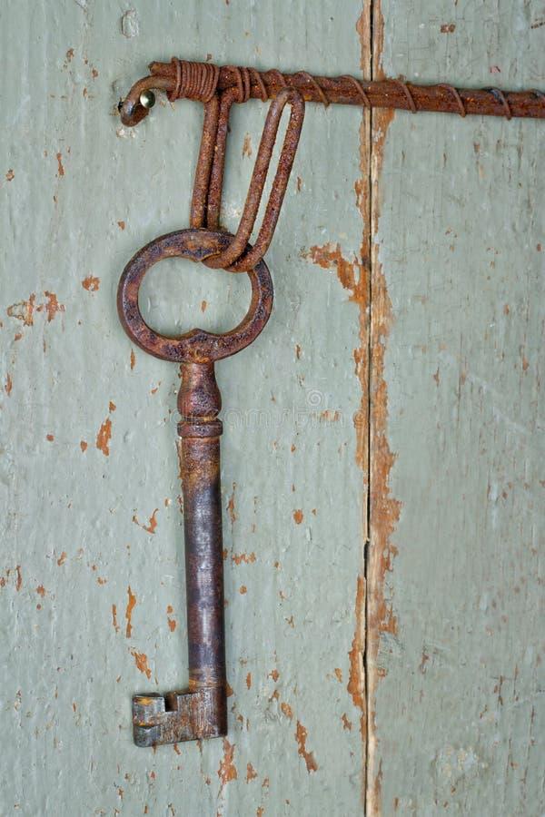 Antikes Schlüsselhängen am hölzernen Hintergrund stockfotos