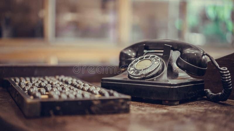 Antikes schwarzes Telefon und hölzerner Abakus stockfotografie