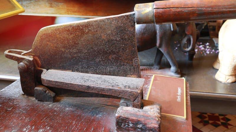 Antikes thailändisches Krautmesser-Zerhackerwerkzeug für trockene Kräuter des Schnittes mit im traditionellen Sanitätshaus stockfotografie