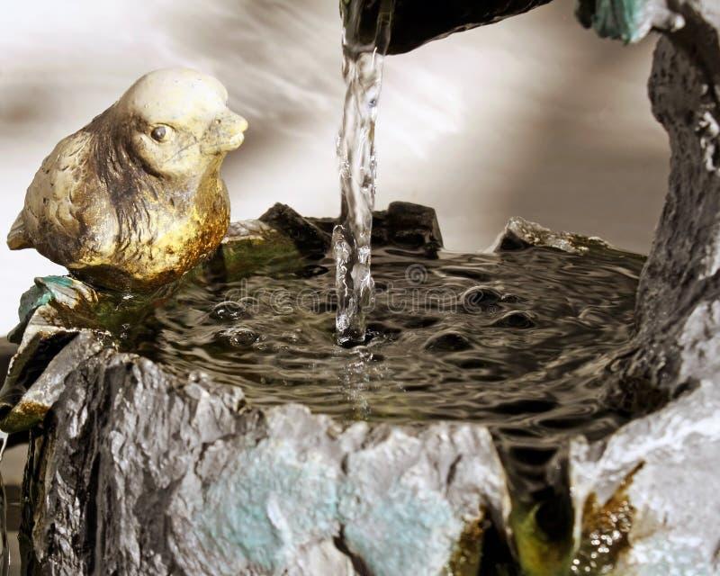 Antikes Vogelbad/Wasserbrunnen mit Steinvogel hockten auf aufpassendem Seitenwasserstrom unten stockfotografie