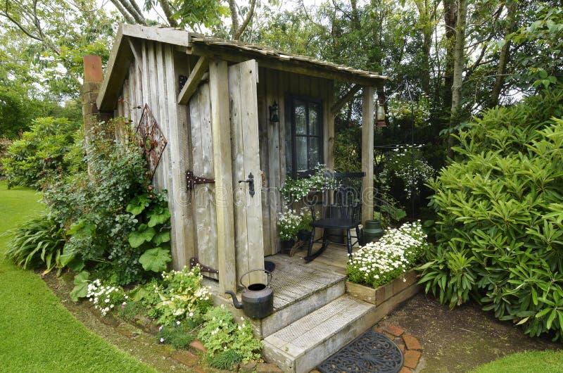 Antikt hyddasammanträde för gullig mycket liten timmer, i att bedöva blommaträdgården royaltyfria bilder