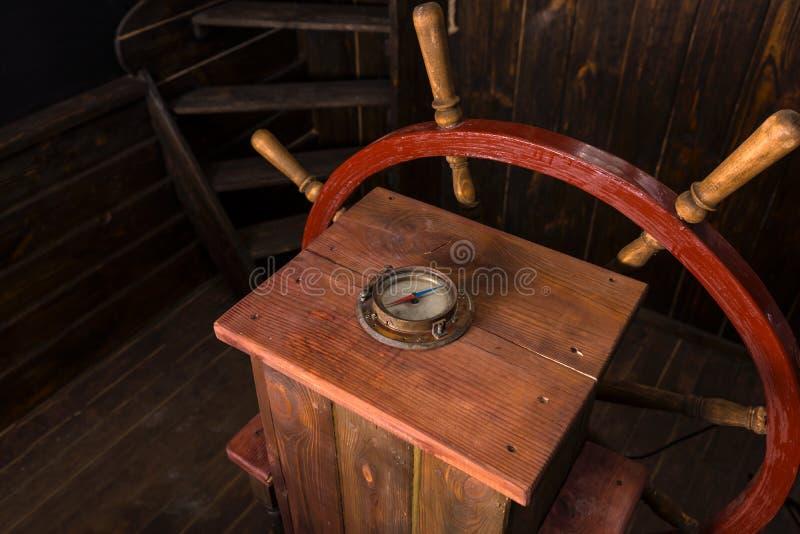 Antikt kompass- och styrninghjul på skeppdäck royaltyfria foton