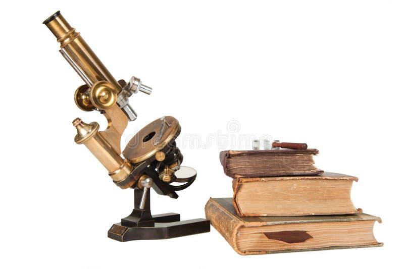 Antikt mikroskop med stängda böcker royaltyfri fotografi