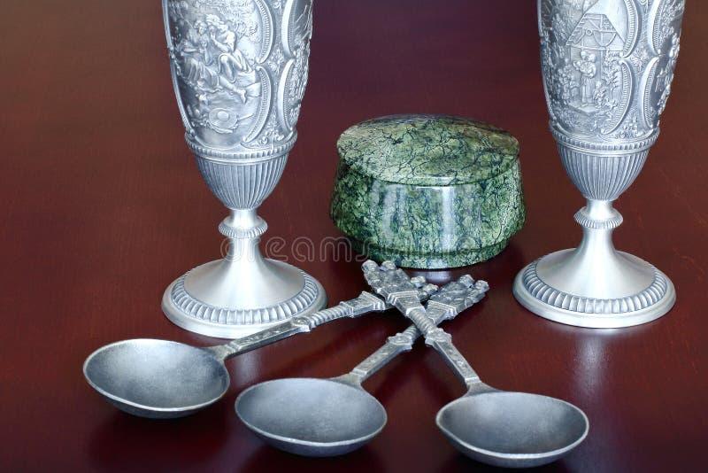 Antikt tenn gjuter vinexponeringsglas, antika metallsoppskedar och rund en ask av den gröna stenen som var slingrande på en brun  arkivbild
