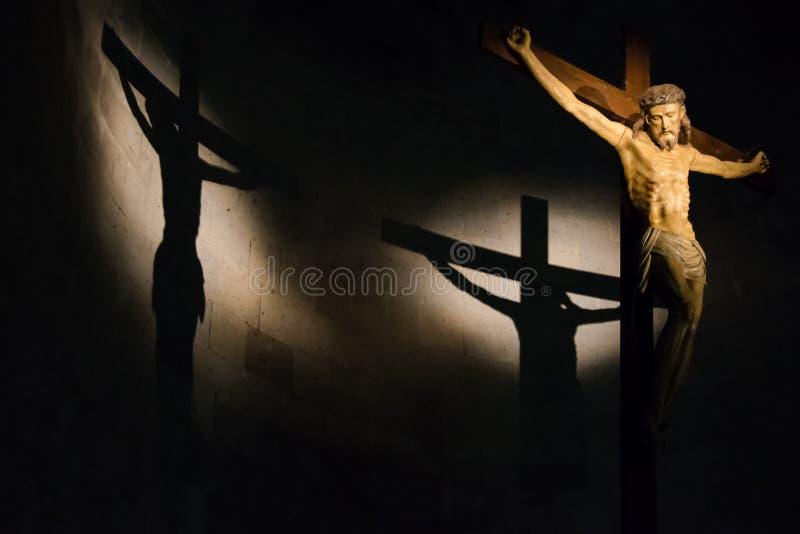 Antikt träkors exponerat inom en historisk italiensk kyrka med skugga som gjutas på väggen arkivbilder