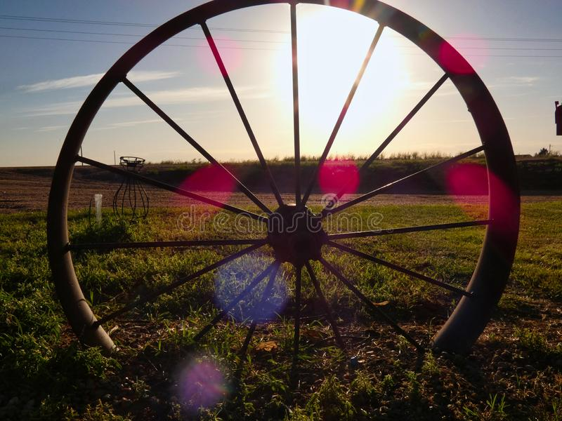 Antikt vagnhjul Silhouetted i solnedgången royaltyfri foto