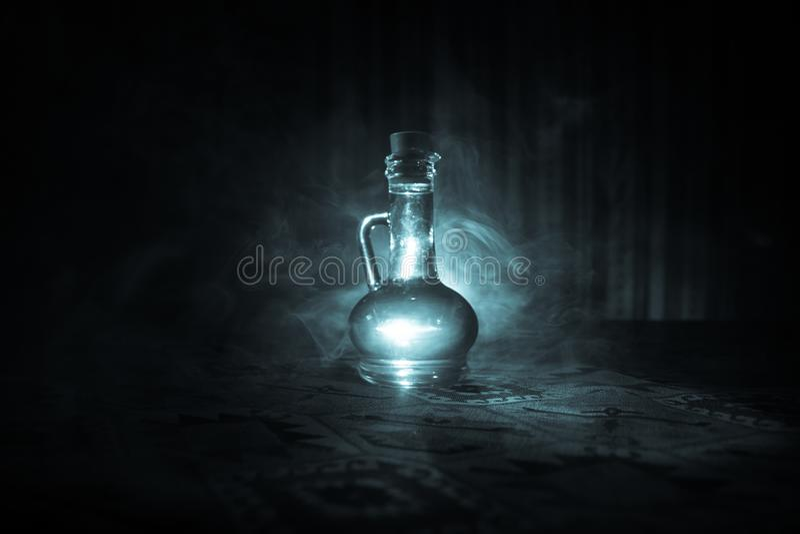 Antikvitet- och tappningglasflaskor på mörk dimmig bakgrund med ljus Gift eller magiflytandebegrepp royaltyfri bild