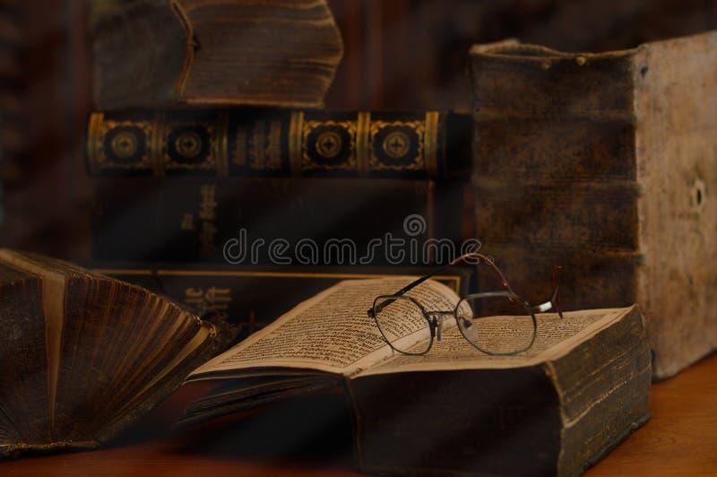 Antikviteten bokar med läs- exponeringsglas i ett dammigt rum royaltyfria bilder