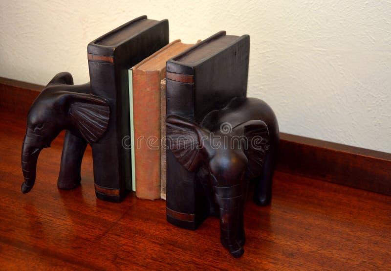 Antikviteten bokar, träelefantbokstöd på den wood tabellen royaltyfria foton