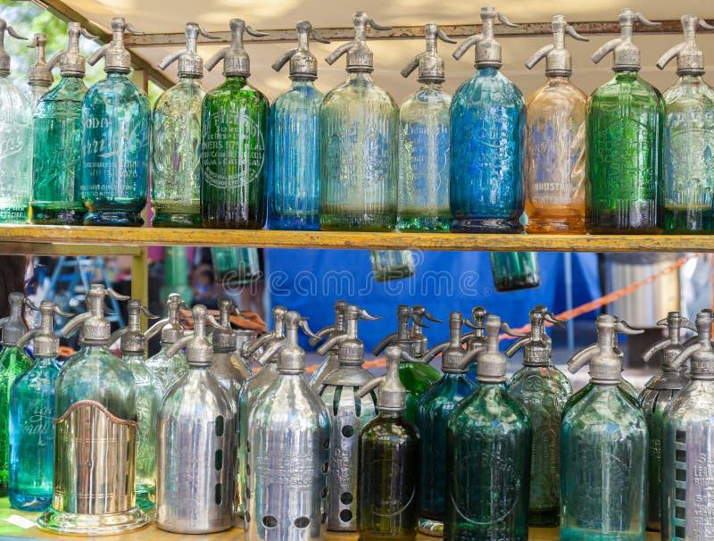 Antikviteten för sodavattenflaskor suger upp genom hävert flaskexponeringsglas på den San Telmo loppmarknaden i Buenos Aires, Arg arkivbilder