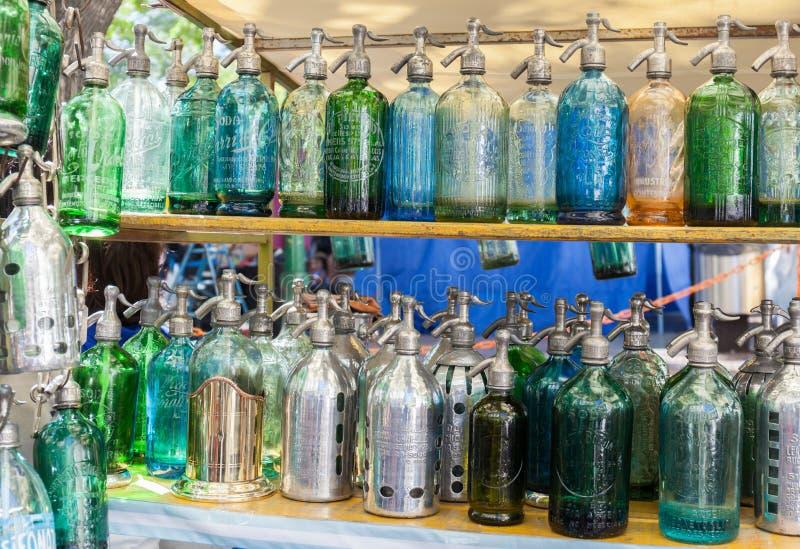Antikviteten för sodavattenflaskor suger upp genom hävert flaskexponeringsglas på den San Telmo loppmarknaden i Buenos Aires, Arg royaltyfria bilder
