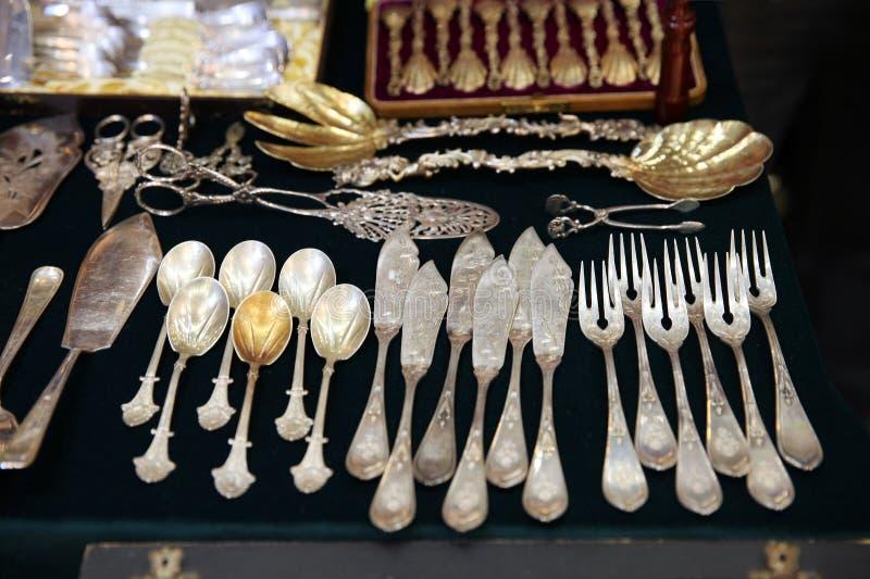 Antikviteten försilvrar bestick, skedar, gafflar, knivar på hyllan av loppmarknaden royaltyfri bild