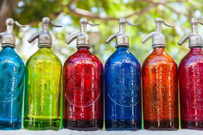 Antikviteten suger upp genom hävert ljusa flaskor, kulört exponeringsglas i loppmarknaden, Buenos Aires, Argentina royaltyfri fotografi