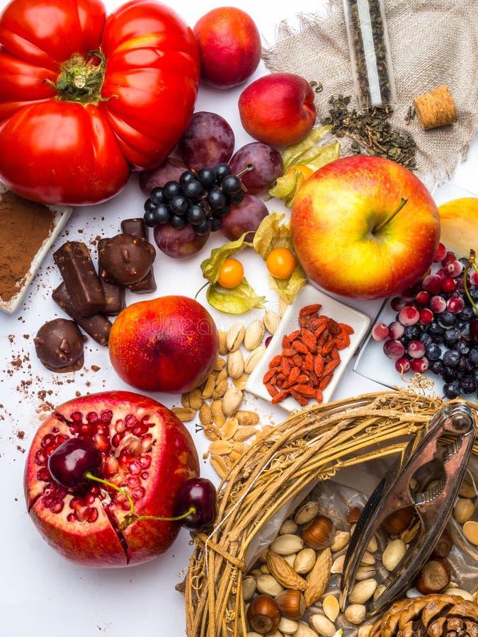 Antioxidantes, comida del resveratrol como té verde, uva, arándano, albaricoque, manzana, cacao, tomates, granada, physalis, oscu fotografía de archivo libre de regalías