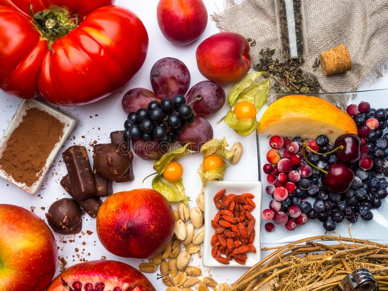 Antioxidantes, comida del resveratrol como té verde, uva, arándano, albaricoque, manzana, cacao, tomates, granada, physalis, oscu fotografía de archivo