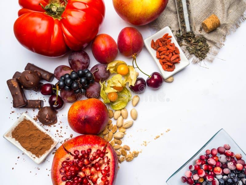 Antioxidantes, comida del resveratrol como té verde, uva, arándano, albaricoque, manzana, chocolate, tomates, granada foto de archivo