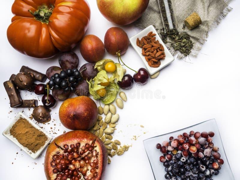 Antioxidantes, comida del resveratrol como té verde, uva, arándano, albaricoque, manzana, chocolate, tomates, granada foto de archivo libre de regalías