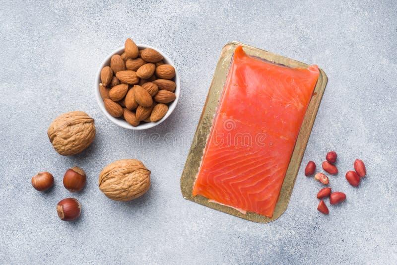 Antioxidantes sanos de los productos alimenticios: pescados y diversos tipos de nueces en un fondo concreto gris imagenes de archivo