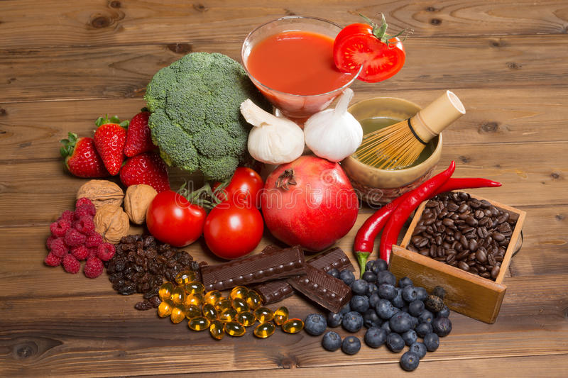 Antioxidants for good health. Healthy antioxidants fruits and vegetables on a wooden table stock images