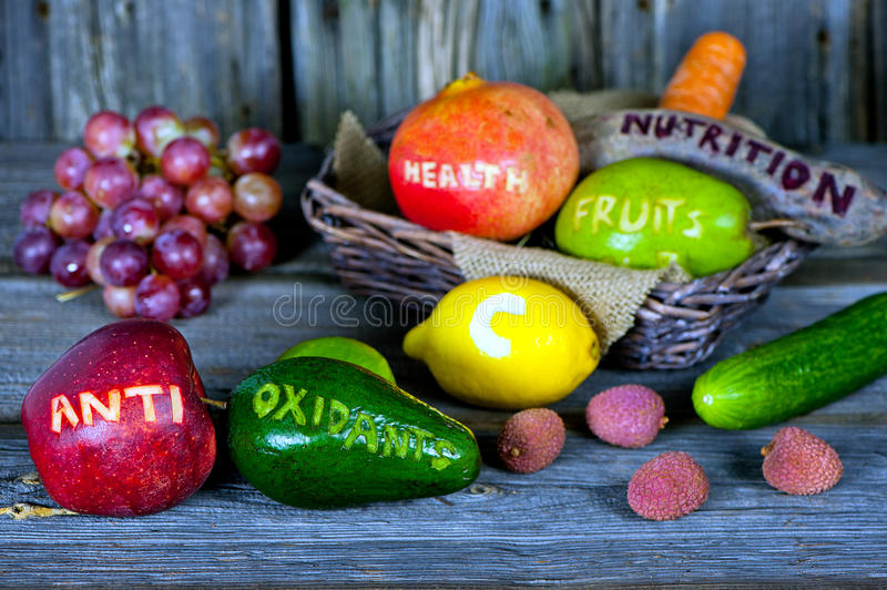 Antioxidants. Scattered fruits and vegetables with cut words - healthy lifestyle concept stock photo