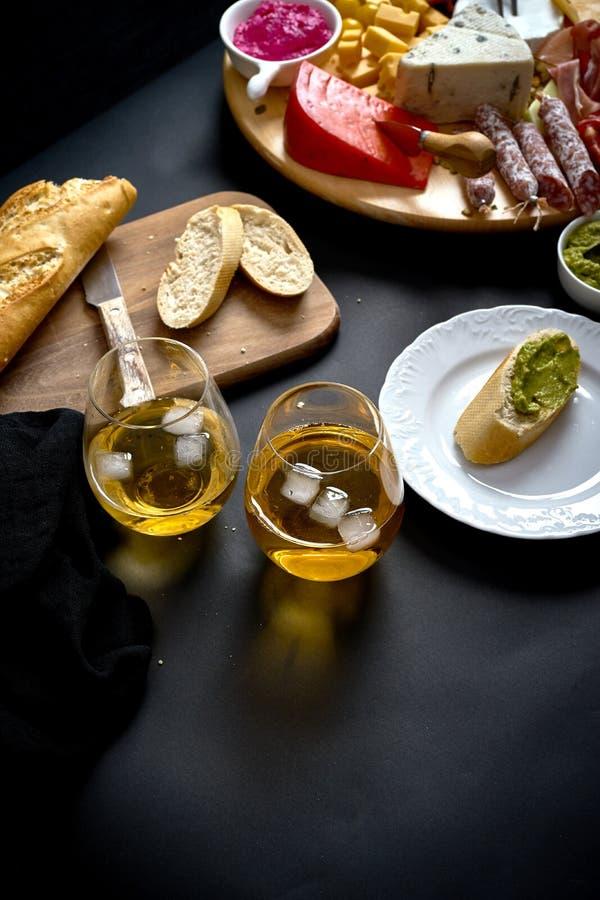 Antipasti всходят на борт с закусками сыра и мяса с белым вином и багетом на борту на черной таблице стоковые фотографии rf
