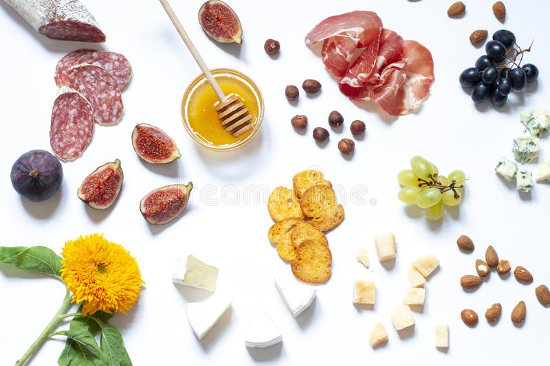 Antipasti food white flat lay with nuts, honey, cured meat, salami, cheeses, grapes and figs. royalty free stock photo