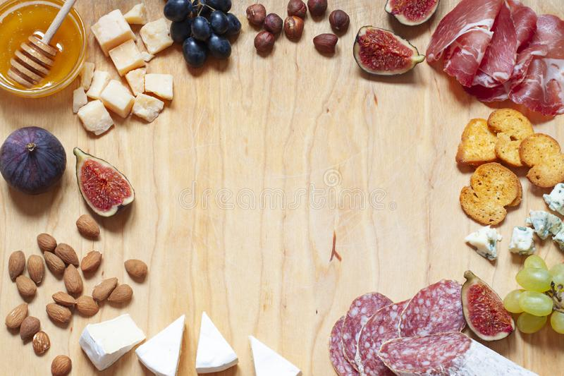 Antipasti food white flat lay with nuts, honey, cured meat, salami, cheeses, grapes and figs on the wooden board. stock image