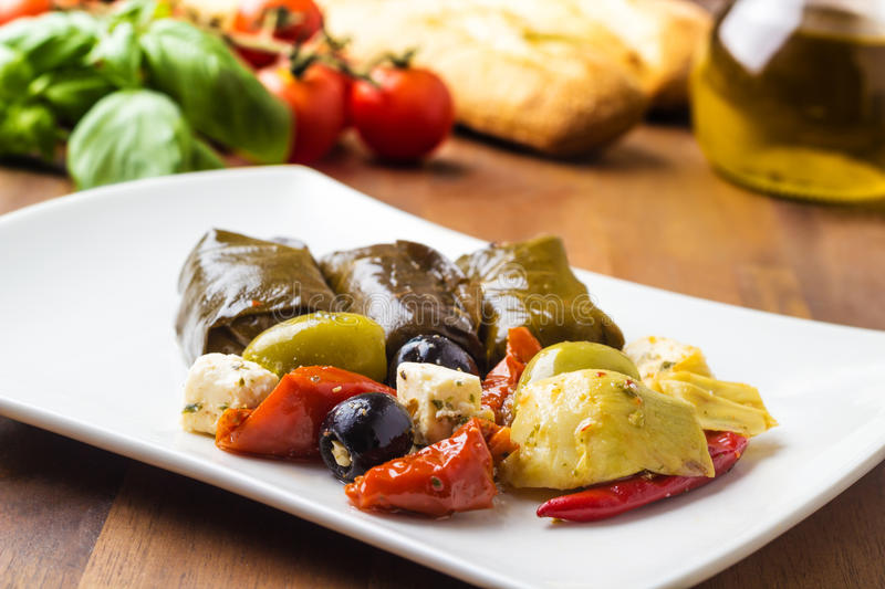 Antipasti. Mixed antipasti plate. Tomatoes, olives and filled grape leaves royalty free stock image