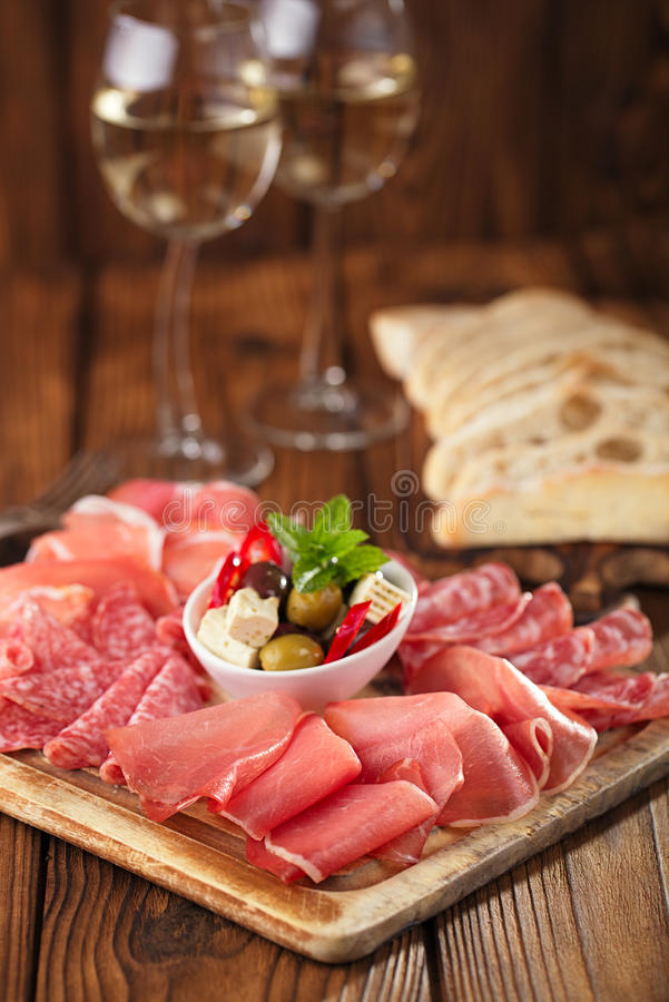 Antipasti Platter of Cured Meat, jamon, olives, sausage, salam. I, ciabatta and white wine glasses on textured wooden table stock photos