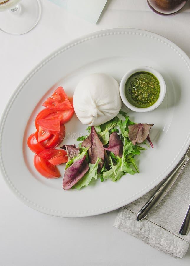 Antipasti saudáveis deliciosos do vegetariano - a salada caprese clássica com tomates, mozzarella com manjericão fresca sae fotos de stock royalty free