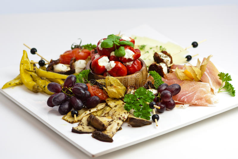 Antipasti variation. Variation of antipasti, olives, mozzarella cheese, chili peppers and tomatoes on a white dish royalty free stock photos