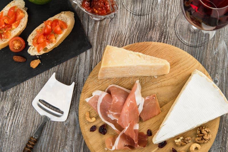 Antipastiuppläggningsfat med jamon och ost på träbräde royaltyfria foton