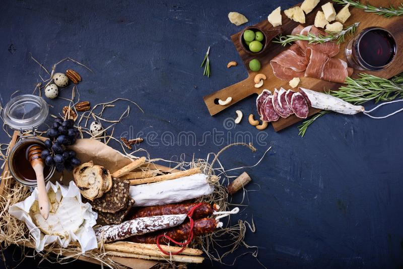 Antipasto appetizer with grape and olives. Top view. Antipasto appetizer with grape and olives. Assortment of meat and cheese snacks. Top view, copy space stock images
