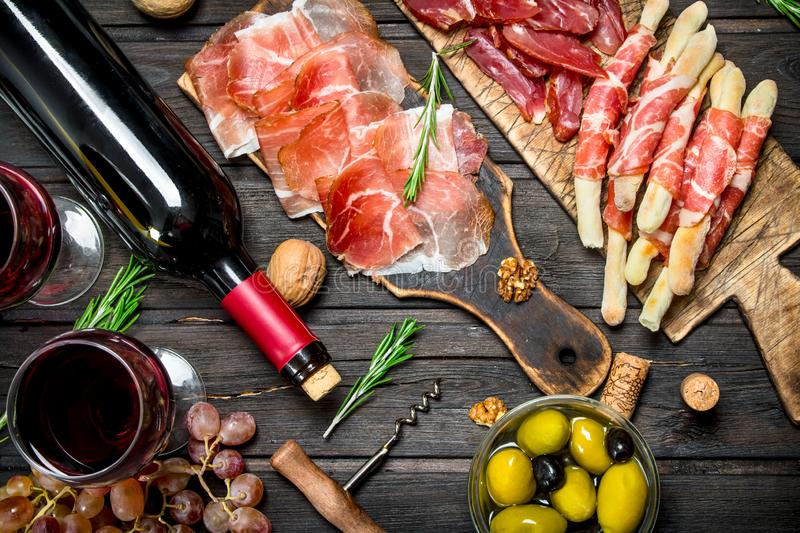 Antipasto background.Various meat appetizer with olives, jamon and red wine. On a wooden background stock image