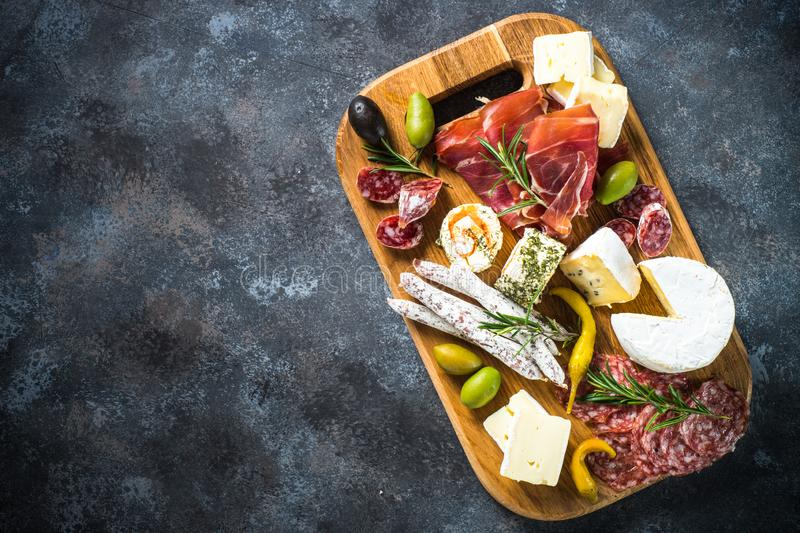 Antipasto board with sliced meat, ham, salami, cheese, olives and red wine. Top view with copy space stock image